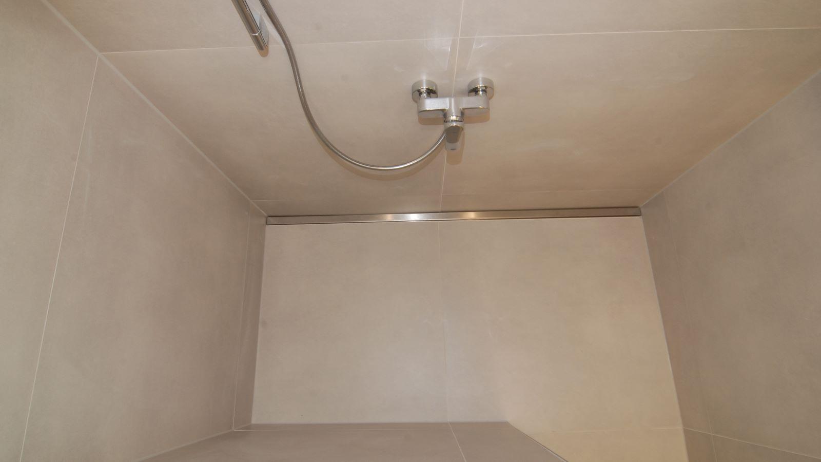 Das bild zeig die aufsicht von oben auf die cm-genaue massanfertigung der langlebigen v4a edelstahl-duschrinne pro. Praktisch und unauffaellig wandbuendig eingebaut an der rueckseite der ebenerdigen dusche traegt sie bei zur ruhigen optik der pflegeleichten dusche.  In diesem sanitaerbereich ist die hygienische reinigung der leicht zu saeubernden duschrinne pro besonders wichtig. Auch die grossformatigen fliesen sind sehr gut zu reinigen. Die duschrinne pro in 100 cm oder 200 cm laenge ermoeglicht das befliesen mit 100 cm x 100 cm bodenfliesen und 100 cm x 300 cm wandfliesen. Die massgefertigte duschrinne pro ist optimal fuer moderne, funktionelle barrierefreie duschen gerade in sanitaerraemen, auch von fitnessstudios oder sportstaetten.
