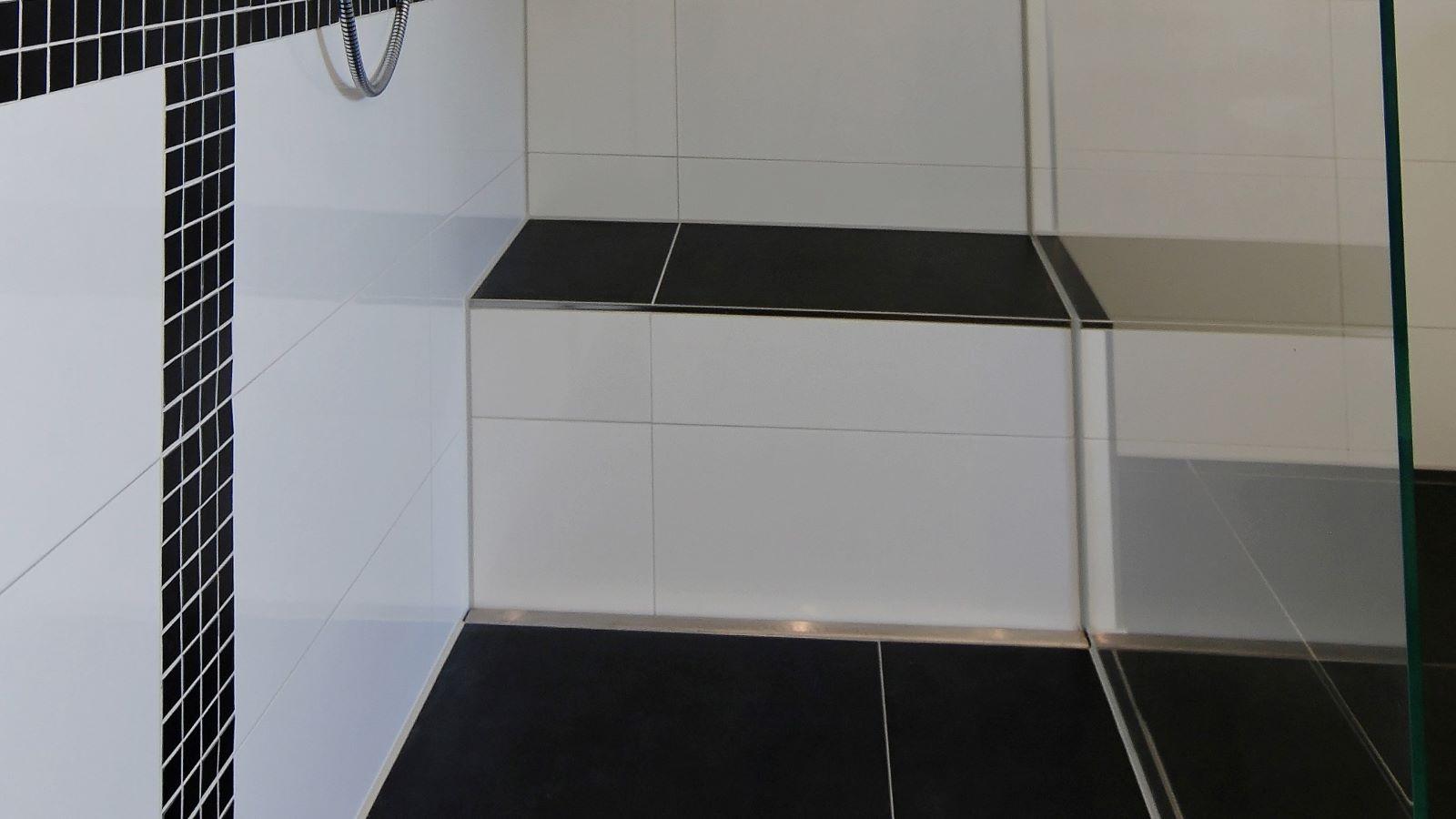 Abgebildet ist die in einer bodengleichen dusche direkt vor einer sitzbank wandbuendig montierte , dezente v4a edelstahl-duschrinne pro. Cm-genau massgefertigt bis 600 cm laenge laesst sich die duschrinne pro einfach zwischen der wand und der glasduschabtrennung montieren. Die unempfindliche duschrinne pro ermoeglicht eine sehr gute linienentwaesserung der ebenerdigen dusche.