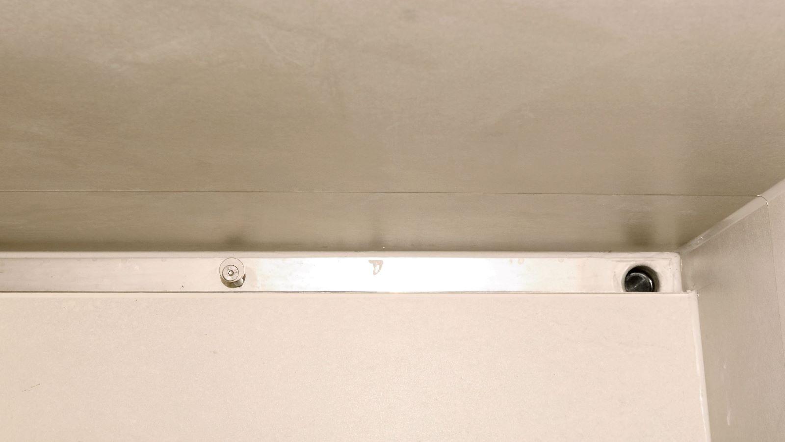 Extra lange, massgefertigte, hochwertige, pflegeleichte v4a edelstahl-duschrinne pro, hier wandbuendig eingebaut in reihendusche im sanitaerbereich. Die sehr hohe ablaufleistung und die freie konfigurierbarkeit des abflusses ermoeglichen eine optimale duschplanung. Hier ist der seitenablauf der flachen duschrinne pro von vorteil. Der ablauf muendet direkt in ein bestehendes abflussrohr.