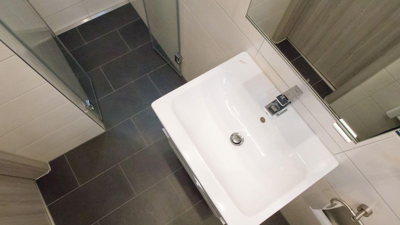 Im abgebildeten Gästebad sieht man die wandbuendig montierte v4a edelstahl-duschrinne pro in der barrierefreien dusche. Cm-genau massgefertigt bis 600 cm laenge laesst sie sich einfach von wand zu wand abschliessend einbauen. Die sehr hohe ablaufleistung, einfache montage, sichere abdichtung und einfache verlegung auch von xxl-fliesen machen die duschrinne pro zur ersten wahl fuer bodengleiche duschen. Einfache pflege der unempfindlichen duschrinne pro sowie hygienische reinigung ohne werkzeug und ohne haarsieb ergaenzen die praktischen vorteile der duschrinne pro.