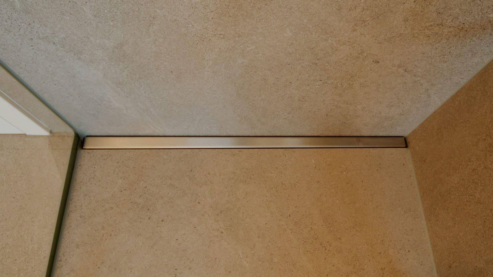 Abgebildet ist eine nahaufnahme der ebenerdigen dusche in moderner optik mit xxl-fliesen. Zur pflegeleichten ausfuehrung dieser barrierefreien dusche traegt die einfach zu reinigende, hochwertige v4a edelstahl-duschrinne pro bei. Form follows function. Dezent wandbuendig an der duschrueckwand eingebaut, schliesst sie passgenau an der glasduschwand links und der duschwand rechts ab. Cm-genaue massfertigung und individuelle sonderanfertigungen der duschrinne pro machen sie zur idealen duschrinne für duschen mit xxl-fliesen.