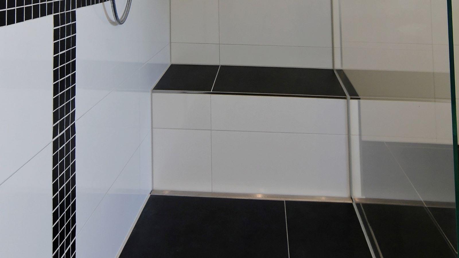 Massgefertigte hochwertige v4a edelstahl-duschrinne pro, direkt vor einer sitzbank eingebaut in bodengleicher dusche mit moderner optik. Grossflaechige bodenfliesen und die passend beflieste sitzbank direkt hinter der dezenten duschrinne pro sowie eine transparente glasduschwand machen diese pflegeleichte dusche zu einem blickfang. Die sehr hohe ablaufleistung der duschrinne pro traegt zur hohen funktionalitaet der dusche bei. In der hier gezeigten barrierefreien dusche wurde eine duschrinnen pro variante eingebaut, die optimal fuer diese dusche individuell gefertigt wurde.