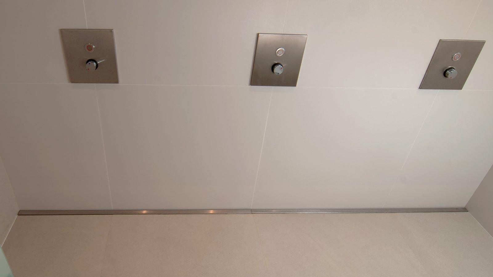 Auf dem foto ist die v4a edelstahl-duschrinne pro in einer reihenduschanlage als wandbuendiger duschablauf eingebaut. Zu sehen ist die extra lange massanfertigung mit der unauffaelligen abdeckung der schmalen duschrinne aus gebuerstetem v4a edelstahl. Die extra flache duschrinne sorgt fuer eine sehr gute linienentwaesserung in der reihenduschanlage, mit drei duscharmaturen, die barrierefrei mit nur einer gefaellerichtung realisiert wurde.