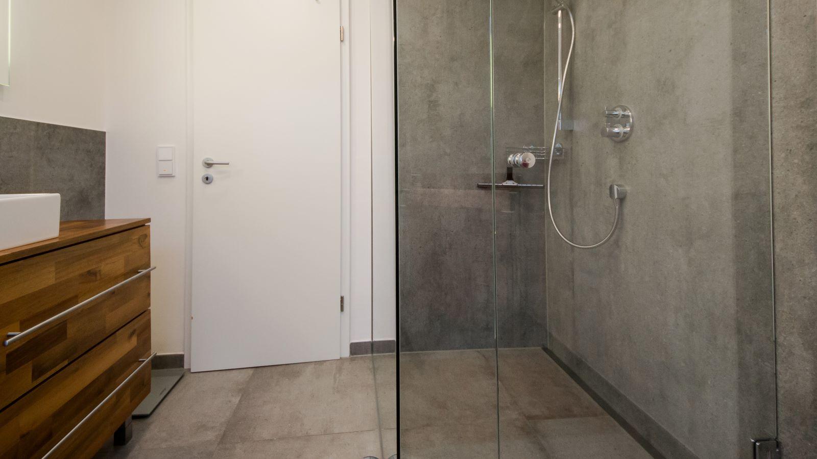 Abgebildet ist die in einer geraeumigen, barrierefreien dusche wandbuendig montierte , extra lange, unauffaellige v4a edelstahl-duschrinne pro. Cm-genau massgefertigt bis 600 cm laenge laesst sich die duschrinne pro einfach zwischen der wand und der glasduschabtrennung montieren. Die unempfindliche duschrinne pro ermoeglicht eine sehr gute linienentwaesserung der bodengleichen dusche. Diese ebenerdige dusche mit xxl-boden- und wandfliesen befindet sich in einem dachgeschossbad.