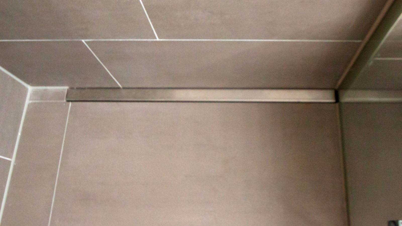 Massgefertigte v4a edelstahl-duschrinne pro mit individuellen seitlichen ausfuehrungen fuer den wandbuendigen einbau. Gezeigt wird die bodenebene dusche mit der unauffaelligen duschrinne pro an der rueckwand eingebaut. Rechts schliesst die massgefertigte duschrinne pro direkt an die glasduschwand an. Die individuelle seitliche ausfuehrung der duschrinne pro ist entsprechend hinten aufkantung fuer wand und rechts kleine aufkantung im rechten winkel fuer glasduschwand.