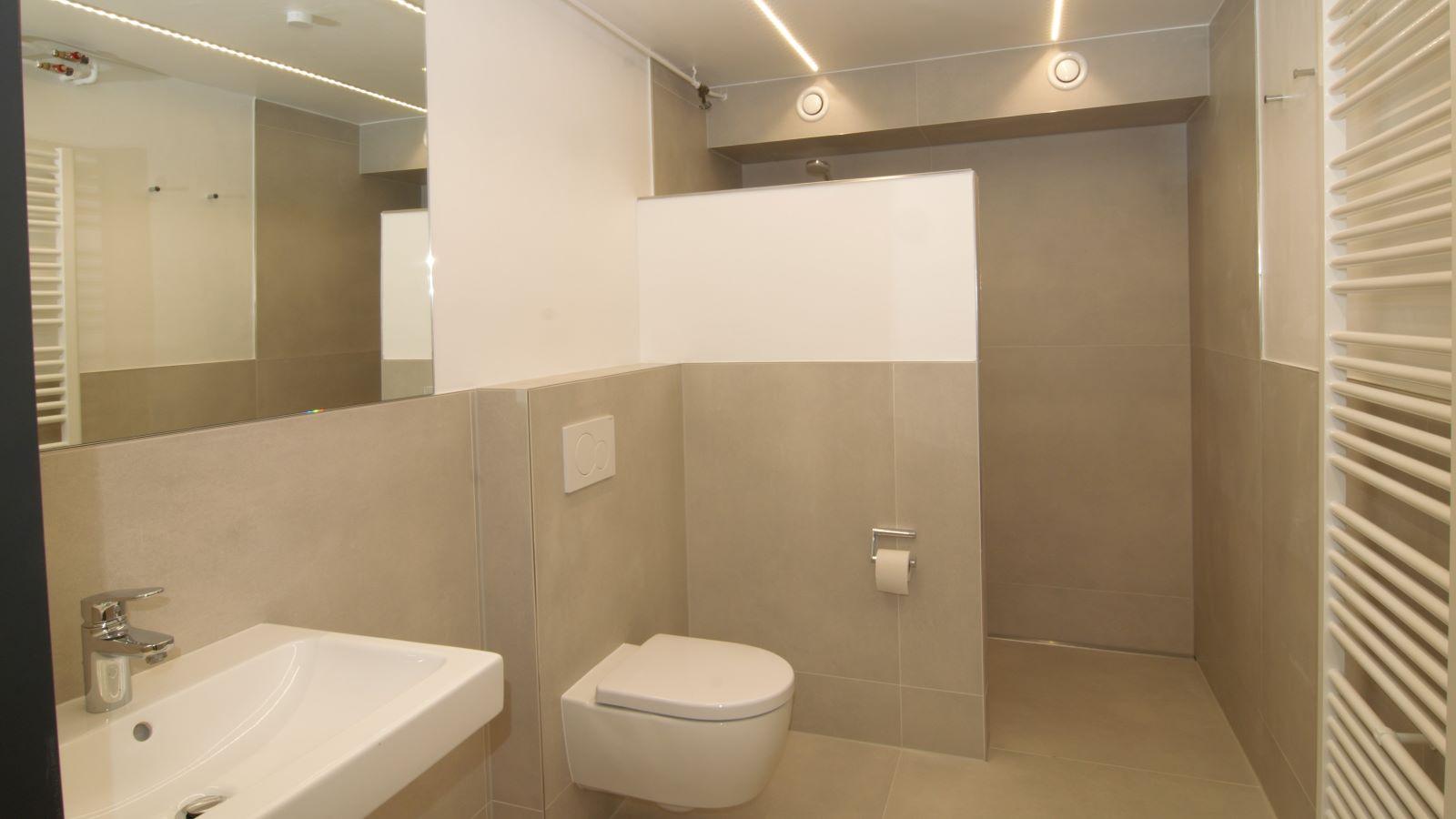 Die abgebildete, barrierefreie walk-in-dusche im sanitaerbereich hat eine wandbuendig montierte v4a edelstahl-duschrinne pro mit seitlichem ablauf zur linienentwaesserung. Die schmale schlitzduschrinne mit der sehr hohen ablaufleistung von ca. 1 l/s erlaubt eine sehr gute duschentwaesserung durch den ebenerdigen bodenablauf.