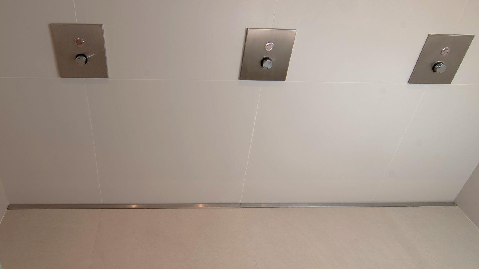 Die hier gezeigte funktionale reihendusche befindet sich in einem fitnessstudio. Die ueber die gesamte rueckwand der reihendusche verlaufende massanfertigung der duschrinne pro ermoeglicht eine einzige gefaellerichtung im boden. Sie garantiert ausserdem eine sehr gute duschentwaesserung. Die im Bild gezeigte, extra lange, hochwertige, pflegeleichte v4a edelstahl duschrinne pro ist wandbuendig in die reihendusche eingebaut. Die dezente abdeckung der duschrinne pro und die grossflaechigen bodenfliesen harmonieren mit der ruhigen optik der wandfliesen