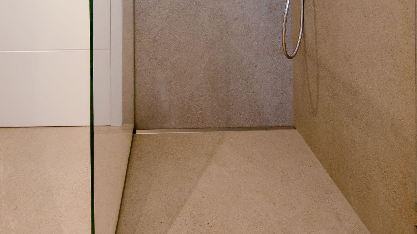 Hochwertige v4a edelstahl-duschrinne pro mit seitlichen ausfuehrungen fuer den wandbuendigen einbau. Gezeigt wird die bodengleiche dusche mit der dezenten duschrinne pro an der rueckwand eingebaut. Links schliesst die massgefertigte duschrinne pro direkt an eine glasduschwand an, rechts direkt an die wand. Die individuelle aufkantung der duschrinne pro ist entsprechend links kleine aufkantung im rechten winkel fuer glasduschwand, hinten aufkantung fuer wand und rechts aufkantung im rechten winkel fuer wandecke.