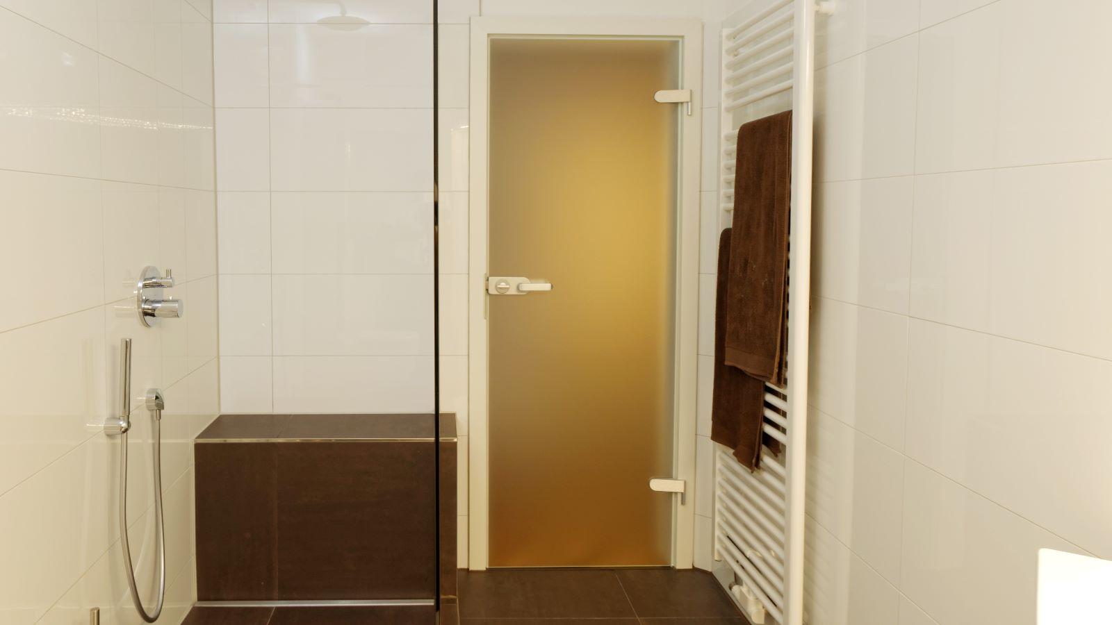 Abgebildet ist die in einer barrierefreien dusche unauffaellig vor einer sitzbank eingebaute, zeitlose v4a edelstahl-duschrinne pro. Cm-genau massgefertigt bis 600 cm laenge, laesst sich die pflegeleichte duschrinne pro einfach zwischen wand und transparenter glasduschwand einbauen. Durch ihre sehr hohe ablaufleistung ermoeglicht die robuste duschrinne pro eine sehr gute linienentwaesserung der bodengleichen dusche. Diese bodengleiche dusche mit grossformatigen boden- und wandfliesen befindet sich in einem kleinen bad.