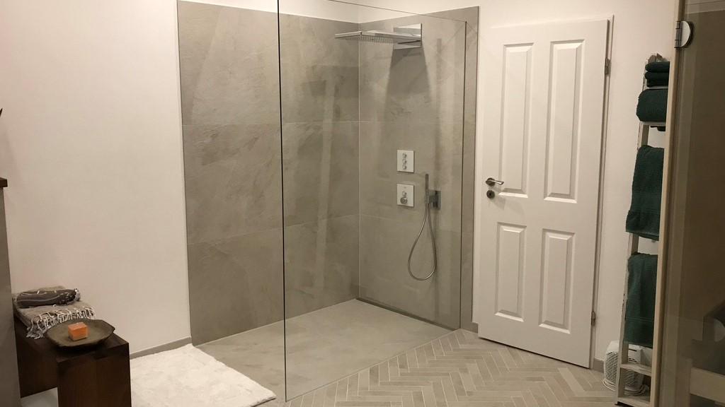 Die abgebildete barrierefreie walk-in-dusche im bad kombiniert mit einer sauna hat eine wandbuendig eingebaute, unauffaellige v4a edelstahl-duschrinne pro. Die sehr flache, maßgefertigte duschrinne pro mit sehr hoher ablaufleistung entwaessert die dusche. Cm-genau massgefertigt bis 600 cm laenge laesst sich die duschrinne pro hier ideal einbauen. Die sehr hohe ablaufleistung, einfache montage, sichere abdichtung und einfache verlegung auch von xxl-fliesen machen die duschrinne pro zur ersten wahl fuer bodengleiche duschen. Einfache pflege der unempfindlichen duschrinne pro sowie hygienische reinigung ohne werkzeug und ohne haarsieb ergaenzen die praktischen vorteile der duschrinne pro.