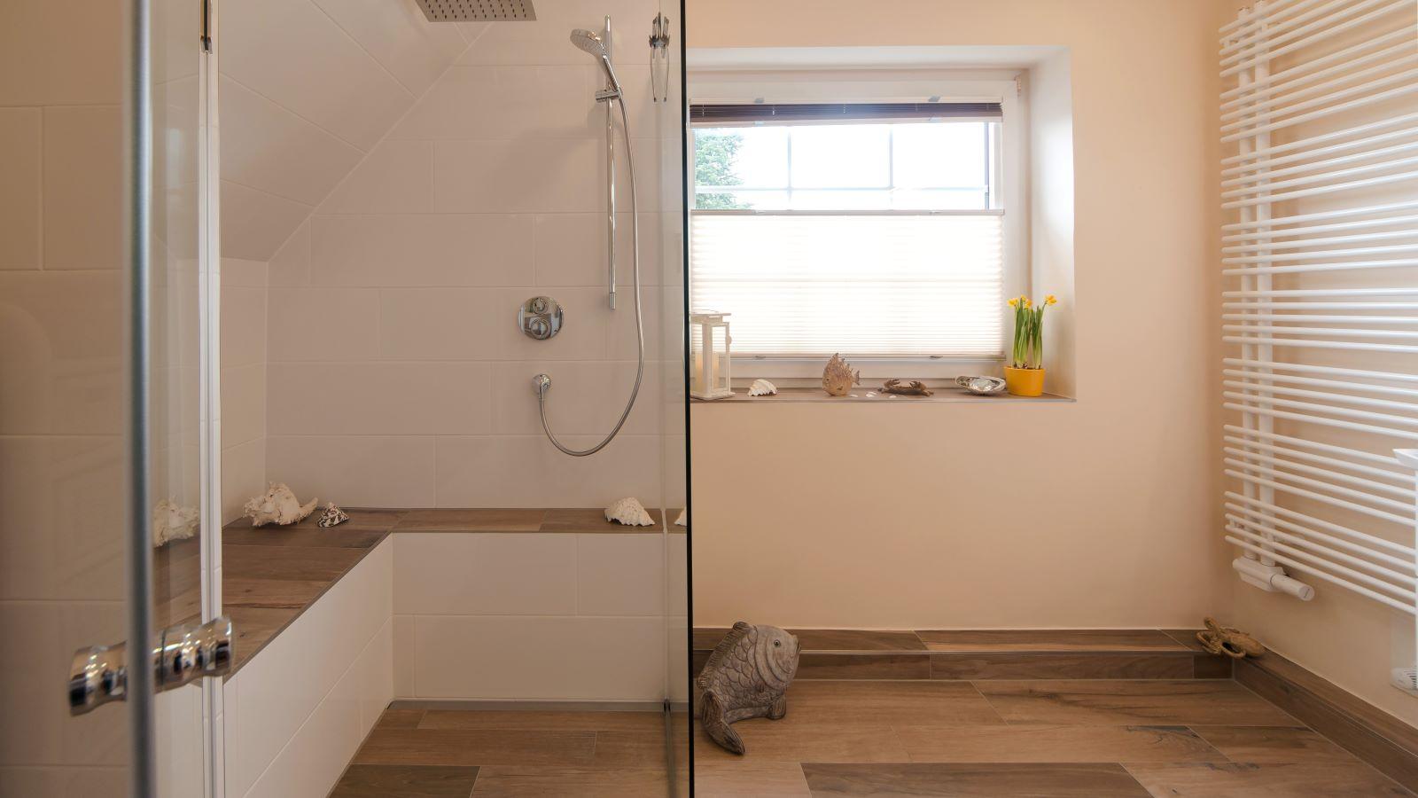 Abgebildet ist die unauffaellige V4a-edelstahl-duschrinne-pro wandbuendig in einer barrierefreien dusche mit sitzbank installiert. Als bodenablauf sorgt sie fuer eine sehr gute linienentwaesserung der ebenerdigen dusche.
