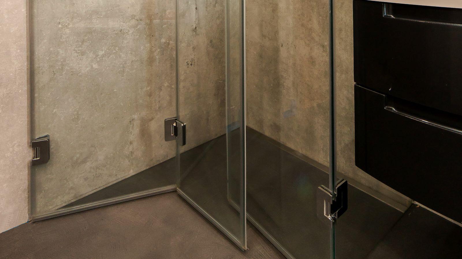 Abgebildet ist die in einer barrierefreien dusche dezent wandbuendig eingebaute, hochwertige v4a edelstahl-duschrinne pro. Cm-genau massgefertigt bis 600 cm laenge, laesst sich die pflegeleichte duschrinne pro einfach zwischen wand und transparenter glasduschwand einbauen. Durch ihre sehr hohe ablaufleistung ermoeglicht die extra flache duschrinne pro eine sehr gute linienentwaesserung der bodengleichen dusche. Diese ebenerdige dusche mit grossformatigen boden- und wandfliesen befindet sich in einem kleinen bad.