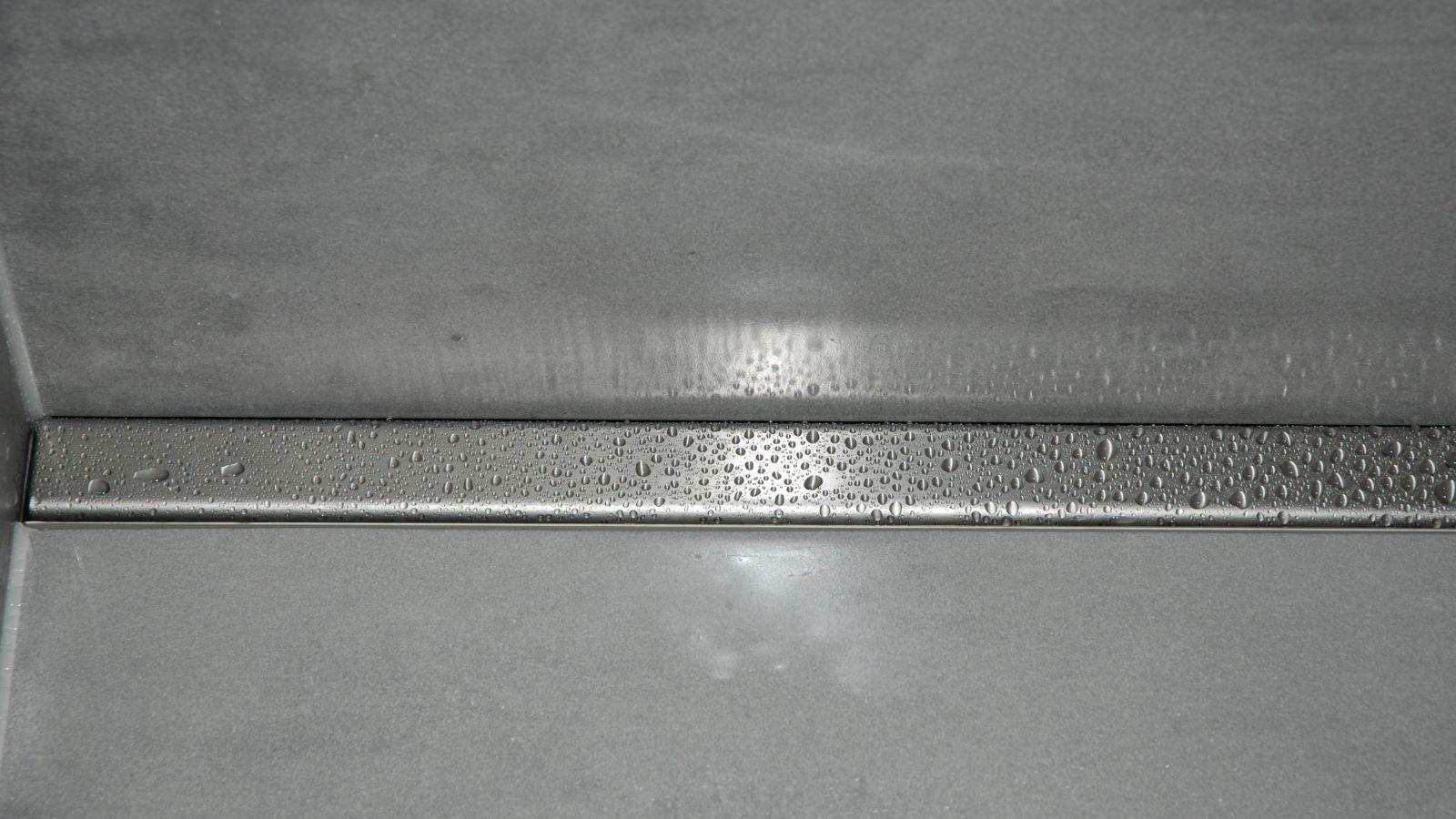 Im Bild sichtbar ist die nahansicht der wandbuendig eingebauten, cm-genauen massanfertigung der hochwertigen v4a edelstahl-duschrinne pro.  Unauffaellig eingebaut an der rueckseite der barrierefreien dusche unterstuezt sie die ruhige optik der pflegeleichten, ebenerdigen dusche. Die elegante abdeckung aus gebuerstetem v4a edelstahl der duschrinne pro und die grossflaechigen wand- und bodenfliesen bewirken eine moderne optik der pflegeleichten, barrierefreien dusche.