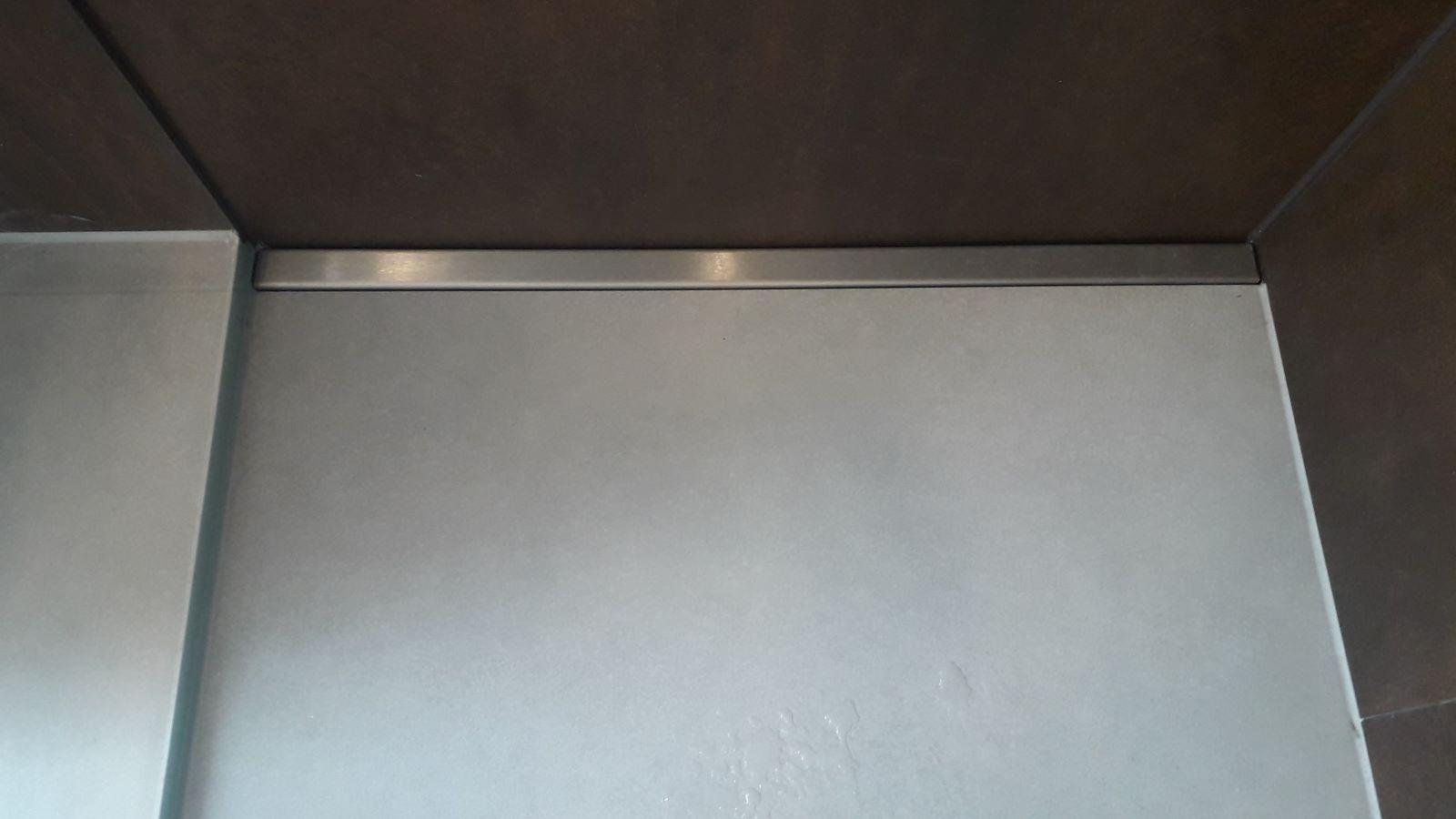 Nahansicht der ebenerdigen, pflegeleichten, begehbaren dusche mit wandbuendiger, extra flacher, langlebiger v4a edelstahl-duschrinne pro massanfertigung. Hier wird die dezente optik der duschrinne pro sichtbar. Dennoch hat sie eine sehr hohe ablaufleistung. Form follows function. Die unauffaellige duschrinne pro bietet einmalige vorteile fuer die moderne gestaltung dieser traumdusche mit grossformatigen xxl-bodenfliesen und durchsichtiger ganzglas-duschwand. Die planung dieser barrierefreien traumdusche mit der massgefertigten duschrinne pro mit sehr geringer einbauhoehe und realisierung im zuge der badmodernisierung im altbau war moeglich trotz holzbalken und heizungsrohren in der geschossdecke. Dieses moderne, trendige bad im dachgeschoss ist pflegeleicht dank der xxl-fliesen an wand und boden und der duschrinne pro, dezent wandbuendig eingebaut. Als optimale duschrinne fuer bodengleiche, altersgerechte duschen im altbau vereint sie massgefertigte, cm genaue laenge, sehr geringe einbautiefe, individuell angefertigter ablauf mit frei bestimmbarer position und richtung sowie sehr hoher ablaufleistung von ca. 1 l/s.