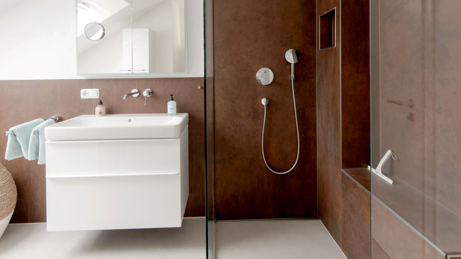 Abgebildet ist eine bodengleiche, pflegeleichte dusche mit wandbuendiger, sehr flacher, hochwertiger v4a edelstahl-duschrinne pro massanfertigung. Die sehr hohe ablaufleistung und dezente optik der duschrinne pro sind vorteilhaft fuer die optimale gestaltung dieser traumdusche mit grossformatigen fliesen und transparenter ganzglas-duschwand. Hier wurden 1 x 1 m xxl-bodenfliesen und 1 x 3 m xxl-wandfliesen verwendet, um die barrierefreie walk-in-dusche modern und pflegeleicht zu gestalten. Durch die unauffaellige, wandbuendig eingebaute duschrinne pro ist ein einseitiges gefaelle in der ebenerdigen dusche moeglich. Dieses modernisierte bad mit xxl-fliesen in warmen brauntoenen ist in einem dachgeschoss nach einer altbausanierung entstanden. Auch bei holzbalken und heizungsrohren als hindernisse in der altbaugeschossdecke ist durch die sonderanfertigung der duschrinne pro die optimale variante der duschrinne pro in massgefertigter laenge, nur 40 mm einbauhoehe und freier abflussposition und ablaufrichtung die realisierung der traumdusche der bewohner moeglich.