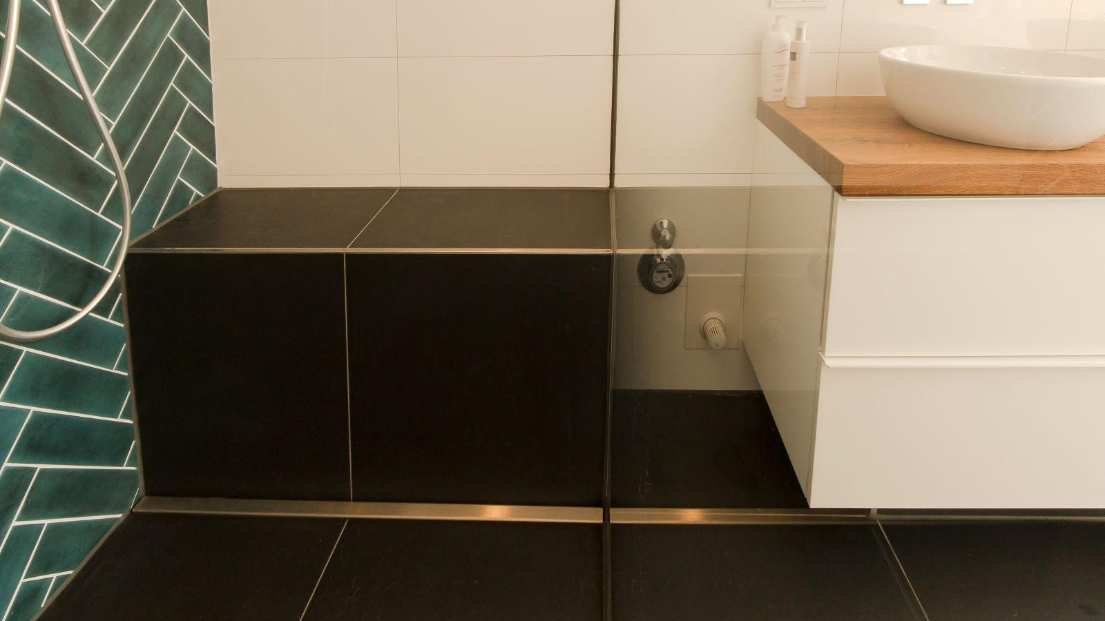 Die abgebildete, barrierefreie walk-in-dusche im luxurioesen bad hat eine direkt vor einer sitzbank montierte v4a edelstahl-duschrinne pro. Die sehr flache, maßgefertigte duschrinne pro ist ideal für diese badsanierung im altbau. Cm-genau massgefertigt bis 600 cm laenge laesst sich die duschrinne pro hier perfekt einbauen. Die sehr hohe ablaufleistung, einfache montage, sichere abdichtung und einfache verlegung auch von xxl-fliesen machen die duschrinne pro zur ersten wahl fuer bodengleiche duschen. Einfache pflege der unempfindlichen duschrinne pro sowie hygienische reinigung ohne werkzeug und ohne haarsieb ergaenzen die praktischen vorteile der duschrinne pro.