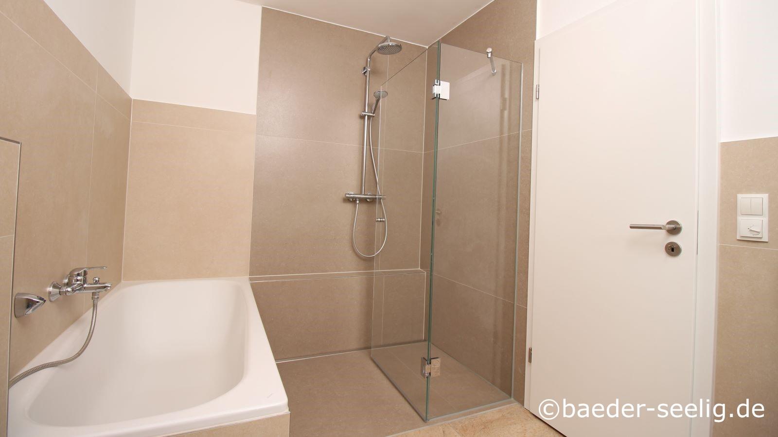 Abgebildet ist noch einmal das badezimmer nach barrierefreier baderneuerung mit badewanne und bodenebener dusche mit glasduschabtrennung und glasduschtuer. Hier ist die duschtuer nach innen eingeklappt.