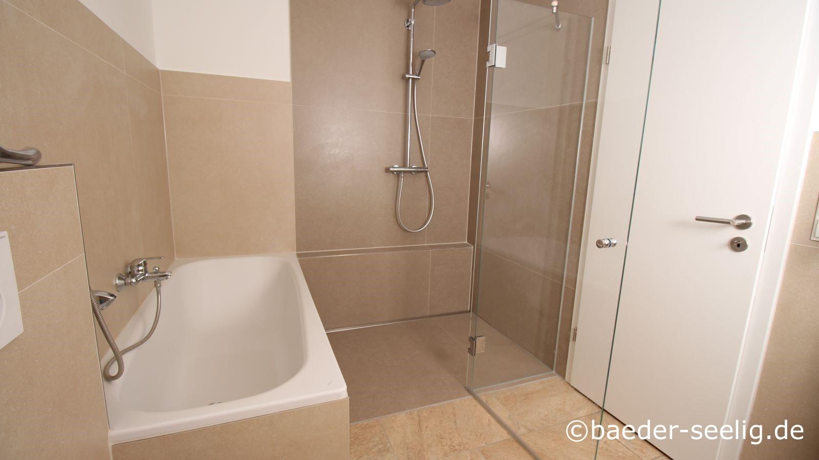 Abgebildet ist ein badezimmer nach barrierefreier badsanierung mit badewanne und bodengleicher dusche mit glasduschabtrennung und glasduschtuer. Die wandbuendig eingebaute, extra flache v4a edelstahl-duschrinne pro ist eine cm-genau in der laenge gefertigte sonderanfertigung, die diese geraeumige dusche als bodentiefe ausfuehrung zwischen der badewanne links und der wand rechts ermoeglicht. Hier ist die duschtuer nach außen eingeklappt.