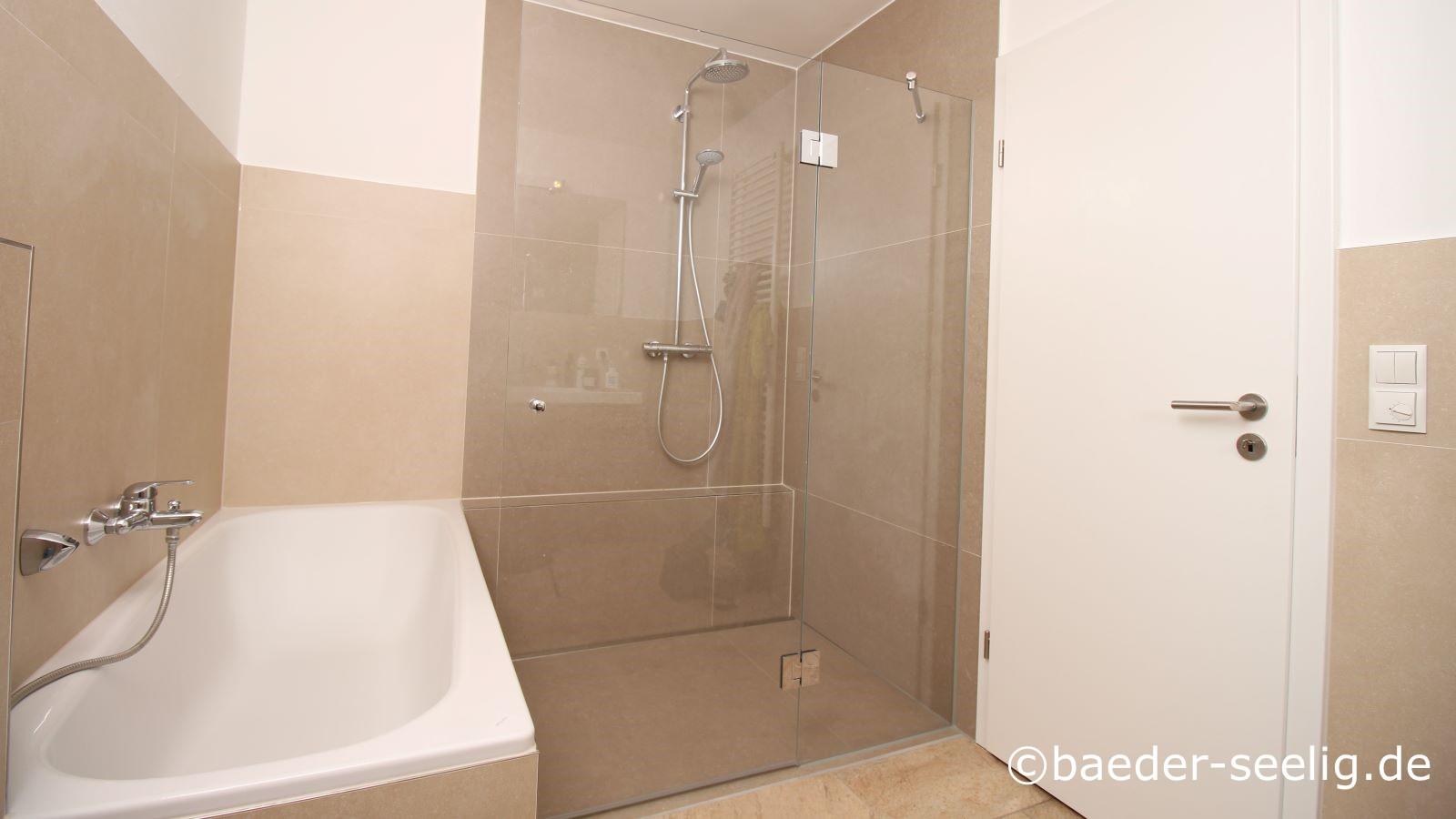 Abgebildet ist dasselbe bad nach barrierefreiem badumbau mit badewanne und ebenerdiger dusche mit glasduschabtrennung und glasduschtuer. Hier ist die duschtuer geschlossen.