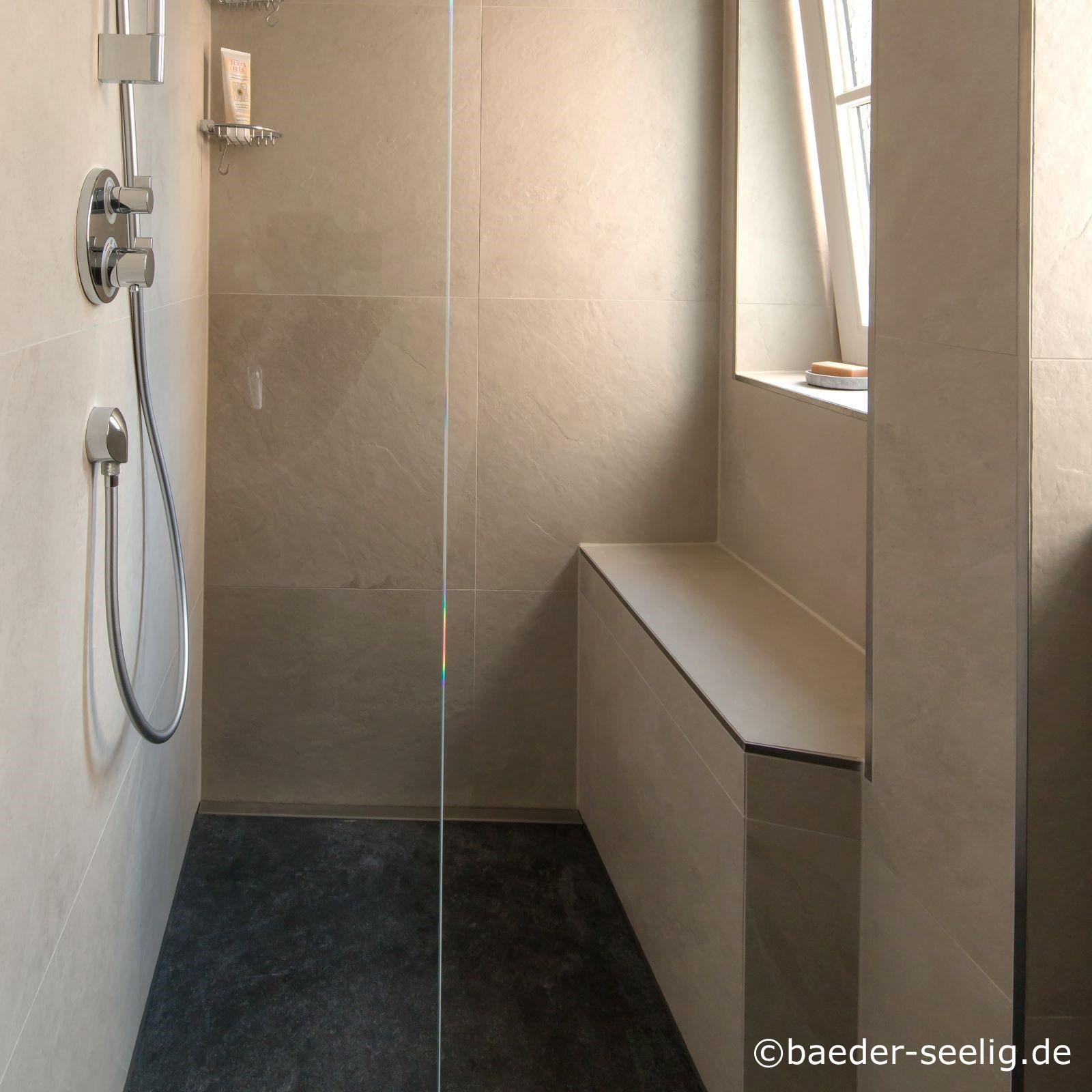 Abgebildet ist eine begehbare duschkabine nach mass in einer wandnische, die vorne links mit einer schmalen ganzglas-duschabtrennung als spritschutz versehen ist. Das bad ist an den waenden mit hellbrauen kerlite xxl feinsteinzeugfliesen und auf dem boden mit schwarzen kerlite xxl feinsteinzeugfliesen gefliest. Rechts in der dusche unter dem badfenster befindet sich eine duschbank. Die bodentiefe duschkabine ist mit einer hand- und einer regenbrause ausgestattet. Die an der duschrueckwand wandbuendig eingebaute duschablaufrinne sorgt mit ihrer sehr hohen ablaufleistung von ca. 1 l/s fuer einen sehr schnellen ablauf des wasserschwalls aus der rainshower dusche. Die in der optimalen sonderanfertigung cm-genau angepasste bodenablaufrinne ermoeglichte die einfache herstellung eines einseitigen gefaelles und damit des einfachen verlegens der xxl fliesen. Zudem machte sie durch ihre sehr geringe einbauhoehe als flachste duschrinne nach mass erst den einbau einer bodengleichen dusche hier im altbau trotz der sehr geringen zur verfuegung stehenden aufbauhoehe moeglich.