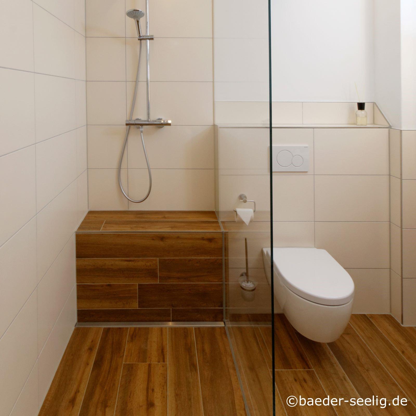 Abgebildet ist eine begehbare dusche links im bild in einer wandecke, rechts davon das weisse wc. Die ganzglas-duschabtrennung ist genau an der linken seite des umfliesten wc-spuelkastens gesetzt worden. Der boden und die duschbank hinten in der bodentiefen dusche sind in holzoptik gefliest, die waende mit einer weissen grossen fliese. Die v4a edelstahl-duschrinne wurde in dieser badrenovierung im baubestand ausgewaehlt, da sie als flachste bodenablaufrinne nach mass cm-genau in der genau passenden sonderanfertigung fuer diese dusche konfiguriert werden konnte. So war auch die einfache herstellung des einseitigen estrichs und einfache verlegung grosser fliesen im bodenbereich der walk-in-dusche nach mass moeglich.