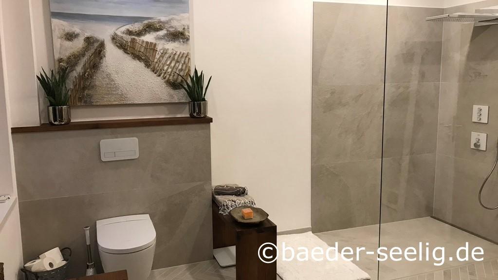Abgebildet ist eine geraeumige walk-in-dusche, die beim badumbau in den privaten spa-bereich nachtraeglich eingebaut wurde. Individuell massgefertigt mit passgenauer laenge und wandaufkantungen machte die v4a edelstahl-duschrinne pro mit nur 40 mm einbauhoehe diese bodengleiche dusche moeglich. Die xxl fliesen im trendigen betonlook an wand und boden konnten durch die individuellen wandaufkantungen der duschablaufrinne einfach verlegt werden. Das wc in dem grossen raum ist ebenfalls sichtbar. Einseitiges gefaelle im bodenbereich der begehbaren dusche und sehr hohe ablaufleistung der duschrinne pro sorgen fuer schnellen abfluss des wassers aus der grossen regenbrause.