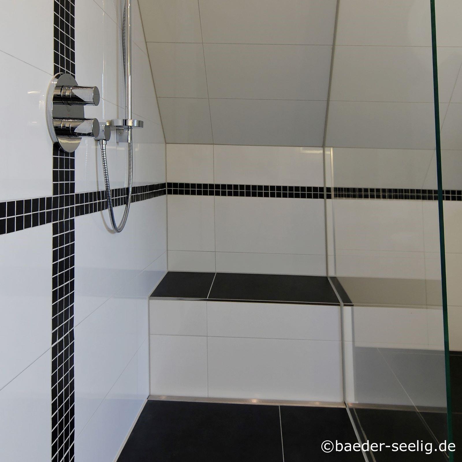 Abgebildet ist eine geraeumige walk-in-duschkabine nach mass, die in eine dachschraege eingebaut wurde. Sie ist unter der schraege, also hinten vom auge des betrachters aus, mit einer duschbank versehen. Diese ist oben mit schwarzen grossen fliesen gefliest, genau wie der boden, und vorne mit weissen grossen fliesen, genau wie die waende. Die cm-genaue massanfertigung der v4a edelstahl-duschrinne pro ist direkt vor der duschbank montiert passgenau zwischen wand und ganzglas-duschabtrennung. Als flachste bodenablaufrinne nach mass wurde sie hier ausgewaehlt, um die bodentiefe dusche nachtraeglich im baubestand einzubauen trotz der sehr geringen zur verfuegung stehenden aufbauhoehe. Mit ihres sehr hohen ablaufleistung von konstant ca. 1 l/s eignet sie sich hervorragend fuer begehbare duschkabinen. Sie ermoeglicht auch die einfache herstellung des einseitigen gefaelleestrichs auf dem boden des duschbereichs, der die einfache verlegung der grossen fliesen mit nur wenigen fugen moeglich machte.