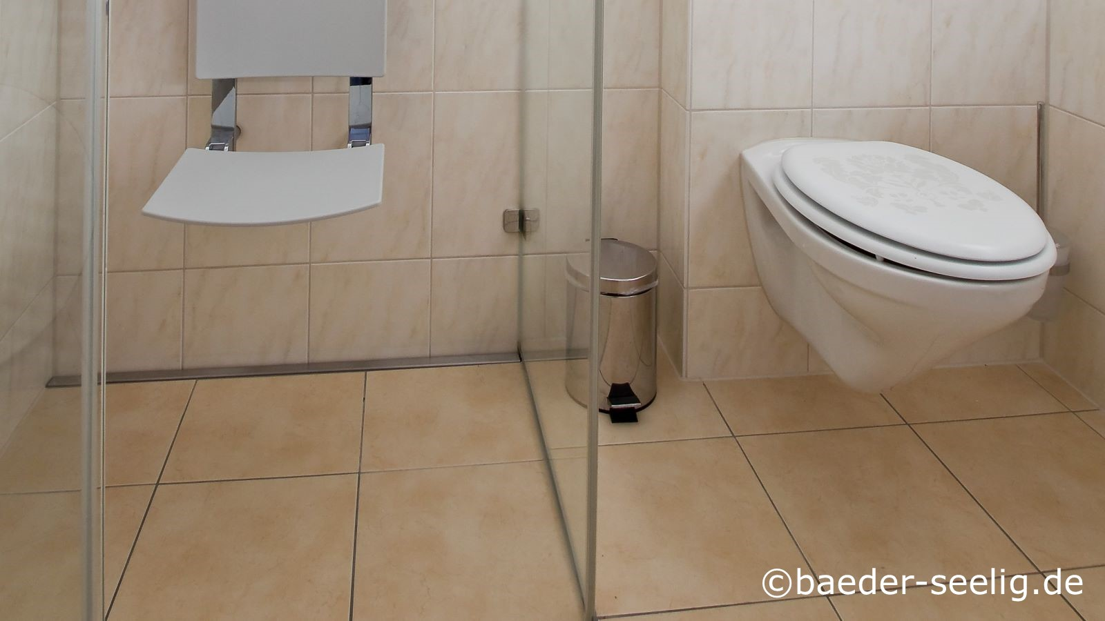 Abgebildet ist eine behindertengerechte, komfortable duschkabine mit duschklappsitz links und ein behindertengerechtes wc mit hohem wc sitz rechts. Wie im anderen behindertengerechten bad auf dem vorigen foto ist die extra flache v4a edelstahl-duschrinne pro mit nur 40 mm einbautiefe wandbuendig von der linken duschwand bis zur glasduschabtrennung rechts passgenau montiert. Die super flache duschablaufrinne nach mass wurde wieder in der optimalen variante eingebaut. Die vorteile, die dieses gerade fuer ein alters-, senioren oder behindertengerechtes bad mit sich bringt sind wie im letzten foto geschildert: Grosse, pflegeleichte  fliesen konnten verlegt werden, man sieht die langlebige, dezente, schmale, robuste abdeckung des duschablaufs, auch sie ist ausgesprochen reinigungsfreundlich. Schwellenfreies durchfliesen mit grossformatigen bodenfliesen ist wesentlich fuer barrierefreie baeder, das ist hier moeglich dank der duschrinne pro in ihrer optimalen variante fuer diese duschplanung.