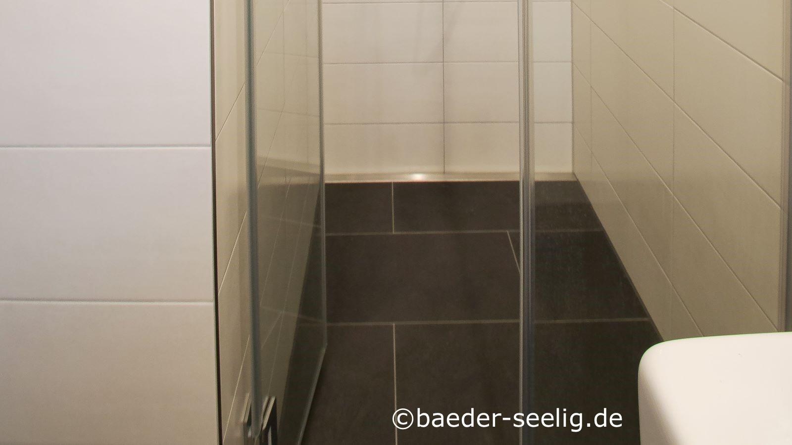 Abgebildet ist eine bodenebene duschkabine mit glasduschtuer in einer wandnische.  Ueber die gesamte rueckseite der dusche ist die schmale, dezente v4a edelstahl-duschrinne pro eingebaut, die mit nur 40 mm einbautiefe und cm-genau nach mass gefertigt diese nachtraeglich installierte ebenerdige dusche ermoeglichte. Die grossformatigen weissen fliesen an der wand und schwarzen fliesen auf dem boden sorgen zusammen mit der glasduschtuer und der langlebigen duschrinne pro fuer ein robustes und pflegeleichtes, modernes bad.