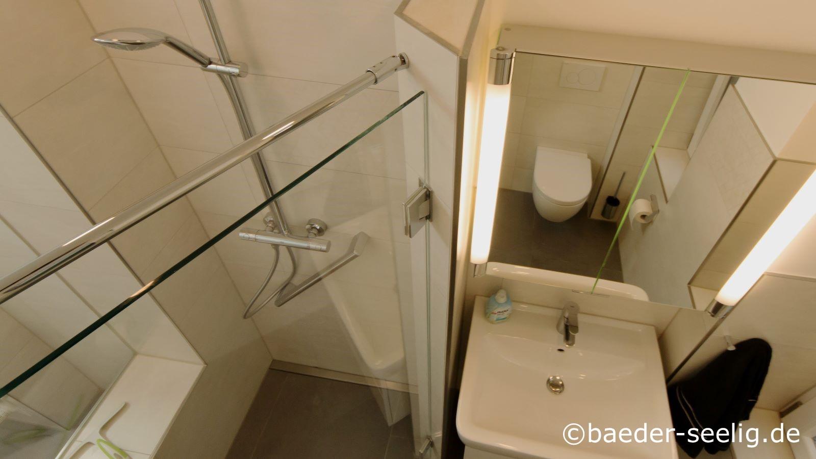 Abgebildet ist eine nachtraeglich waehrend der barrierefreien badrenovierung im altbau nachgeruestete ebenerdige duschkabine nach mass mit einer duschbank. Rechts von der dusche befindet sich der waschtisch mit dem spiegelschrank darueber. Die schmale, dezente v4a edelstahl-duschrinne pro ist passgenau wandbuendig in der wandnische eingebaut worden. Die extra flache duschrinne mit nur 40 mm aufbauhoehe und indidivueller wandaufkantung ermoeglicht die einfache und sichere abdichtung, die einfache herstellung des einseitigen gefaelleestrichs im duschbereich und die einfache verlegung der grossformatigen, pflegeleichten fliesen.