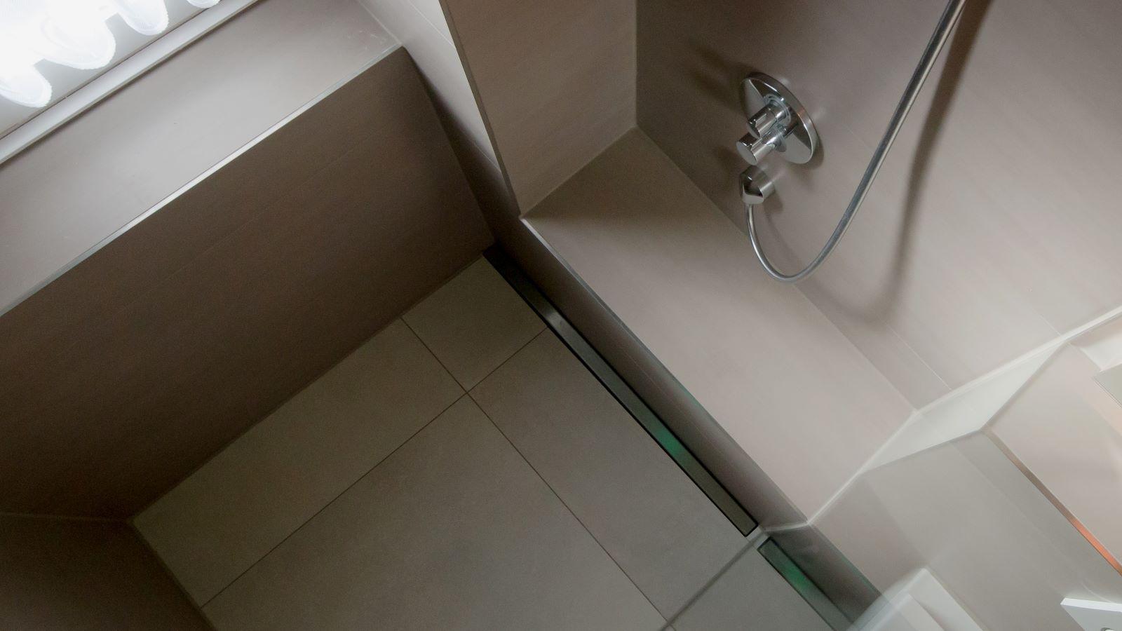 Abgebildet ist die v4a edelstahl-duschrinne pro in einer massgefertigten variante fuer den wandbuendigen einbau in einer barrierefreien duschkabine. Mit den individuellen wandaufkantungen und der kleinen aufkantung fuer die ganzglas-duschwand, die auch auf dem foto sichtbar ist, ist die einfache herstellung des einseitigen gefaelleestrichs und die verlegung der grossformatigen bodenfliesen moeglich, die ebenfalls sichtbar sind.