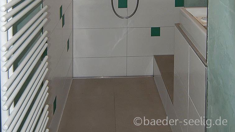 Abgebildet ist eine durch barrierefreien badumbau nachtraeglich installierte begehbare dusche im dachgeschoss. Sie liegt direkt neben dem badfenster. Ueber die gesamte breite der wandnische ist passgenau die cm-genau angefertigte, extra flache v4a edelstahl-duschrinne pro wandbuendig montiert. Davor ist das einseitige gefaelle im duschbereich mit den großformatigen bodenfliesen sichtbar. Auch die waende sind mit grossen, pflegeleichten fliesen befliest. Vorne rechts im bild ist der waschtisch sichtbar, vorne links die hohe badheizung zum trocknen der handtuecher.