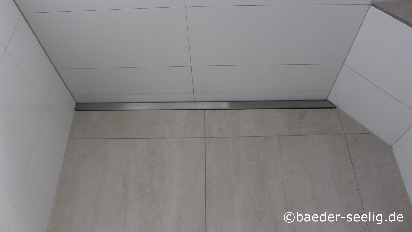 Abgebildet ist die v4a edelstahl-duschrinne pro in einer sonderanfertigung mit 90 Grad winkel links für die standard wandecke und individuellem winkel rechts für eine wandecke in einem anderen winkel. Die duschrinne ist wandbuendig montiert in einer nachtraeglich eingebauten bodengleichen dusche. Die wandaufkantungen der duschbablaufrinne sind ebenfalls individuell ausgefuehrt fuer diese duschplanung.