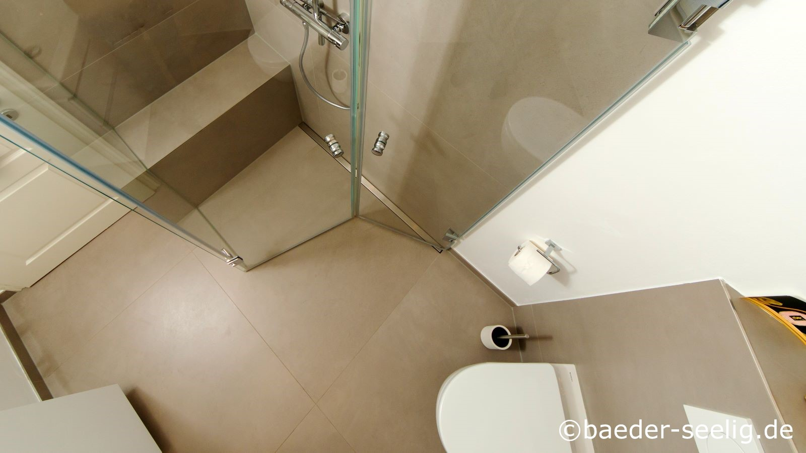 Aus der vogelperspektive sieht man auf diesem foto eine geraeumige duschkabine in einem kleinen bad. Die glasduschtueren sind beide eingeklappt und lassen so viel bewegungsfreiheit im kleinen bad, waehrend die duschkabine nicht genutzt wird.  Rechts vorne ist das wc in der ecke montiert. Die unauffaellige duschablaufrinne ist wandbuendig an der langen seite der dusche montiert. Sie ist ca. 120 cm lang. Es ist eine passgenaue massanfertigung der v4a edelstahl-duschrinne pro mit nur 40 mm einbauhoehe, die genau zwischen wand und glasduschtuer eingebaut ist. Die aufkantungen und seitlichen ausfuehrungen der duschrinne pro ermoeglichten eine sichere und einfache abdichtung, einfache herstellung des einseitigen gefaelleestrichs noch ueber den duschbereich hinaus bis zum wc und die einfache fliesenverlegung. Dieselbe warme, braune farbe der xxl fliesen ist an der wand und auf dem boden verlegt. Das kleine bad wirkt so ruhig und gross, auch konnte die dusche gut in den kleinen raum integriert werden. Durch die wenigen fugen und die hochwertige badausstattung ist das bad auesserst pflegeleicht und langlebig.