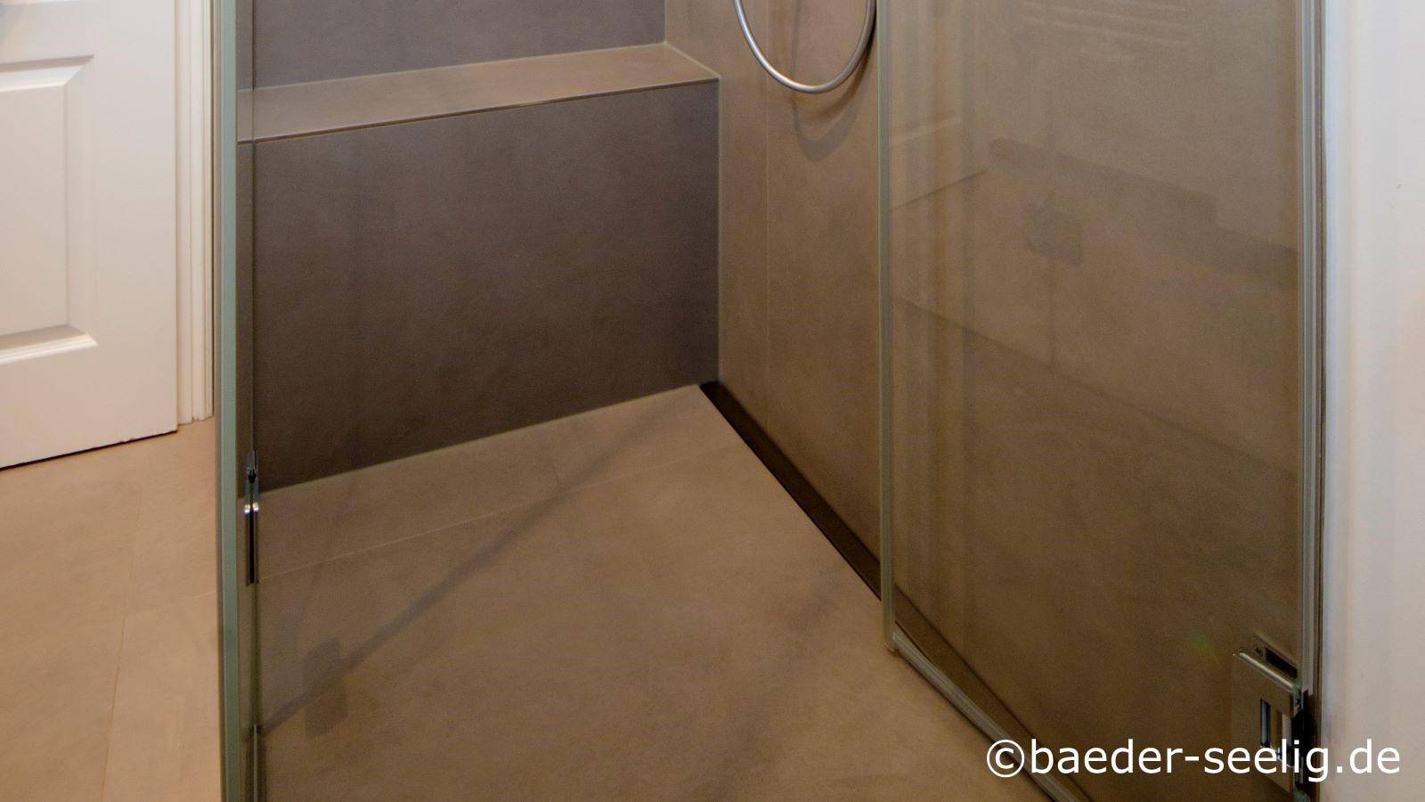 Abgebildet ist die bodengleiche dusche, die im xxl-format mit einer duschrinne pro sonderanfertigung im xxl-format verwirklicht wurde in einem kleinen familienbad mit nur etwa 5 qm grundflaeche. Der clou ist die eingeklappte glasduschtuer, die hier im bild sichtbar ist. Somit kann der platz entweder in der dusche oder aber im bad genutzt werden. Diese loesung ist auch optisch sehr gelungen. Die 1 x 1 m xxl kerlite feinsteinzeug fliesen am boden, die schwellenfrei durchgefliest wurden, tragen ebenso wie die glasduschabtrennung dazu bei, dass die geraumige dusche voellig mit dem kleinen raum verschmilzt. Die 1 x 3 m xxl kerlite wandfliesen machen das kleine bad optisch groesser. Hinten im bild ist die duschbank sichtbar. Die ruhige optik durch die gleichfarbigen braunen kerlite fliesen an wand und boden ist deutlich sichtbar auf dem foto. Mit der aeussert flachen einbauhoehe der v4a edelstahl-duschrinne pro konnte die variante mit nur 40 mm einbauhoehe den nachtraeglichen einbau dieser bodengleiche dusche im bestand ermoeglichen.