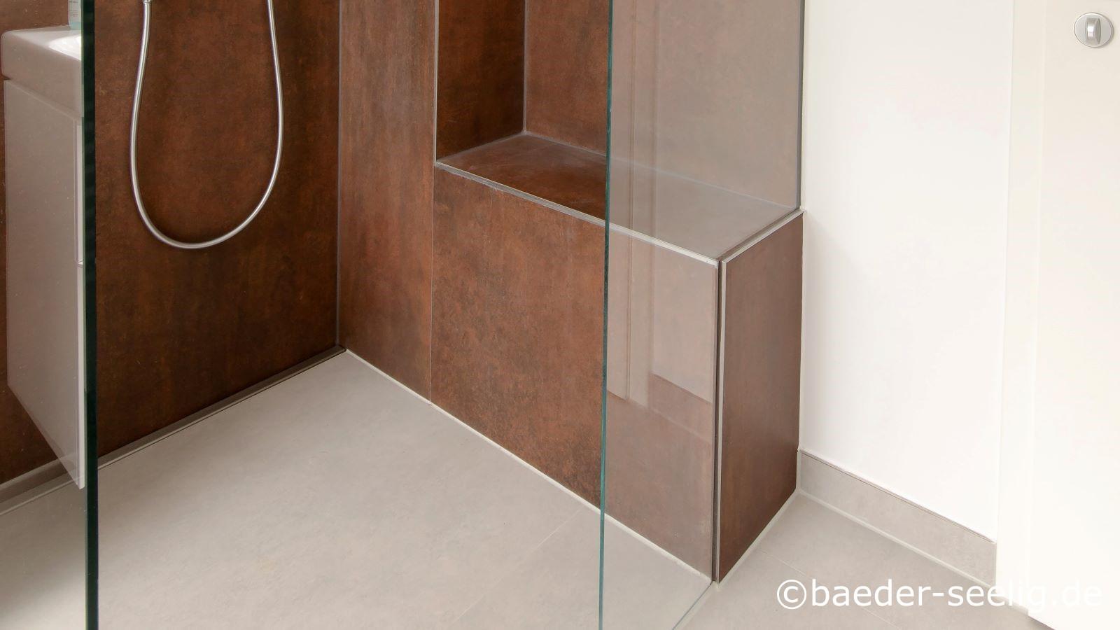 Barrierefreie neugestaltung des badezimmers im altbau realisierte die abgebildete walk-in-dusche. Zu sehen sind die ganzglas-duschabtrennungen, die voellig transparent die begehbare dusche in den raum integrieren und zudem super einfach zu pflegen, robust und langlebig sind. Dasselbe sieht man auch den braunen xxl fliesen an der wand und weissen xxl fliesen auf dem boden an. Das kerlite feinsteinzeug ist sehr hart und kratzfest. Zu sehen ist auch, dass die erdebene dusche fast fugenfrei durch die 1 x 1 m xxl fliesen auf dem boden und der 1 x 3 m xxl fliese an der wand ist. Die massgefertigte duschrinne pro machte durch ihre extra flache einbauhoehe von 40 mm und ihre sonderanfertigung genau fuer diese dusche mit holzbalken als hindernissen in der geschossdecke diese bodentiefe duschkabine moeglich. Auf dem foto ist die einseitige gefaellerichtung im duschbereich sichtbar, den die wandbuedig passgenau zwischen duschwand und duschglasabtrennung eingebaute, massgefertigte duschrinne pro ermoeglicht. Dadurch kann mit den 1 x 1 m xxl bodenfliesen schwellenlos in den duschbereicht durchgefliest werden, so dass auch im bodenbereich die duschkabine nahtlos in den raum integriert ist.