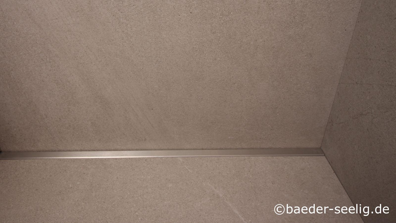 Auf dem foto ist die superflache v4a edestahl-duschrinne nach mass mit extrem geringer einbauhoehe wandbuendig in eine ebenerdige duschkabine eingebaut. Mit nur 20 mm einbauhoehe ist die ultraflache duschrinne pro die flachste erhaeltliche duschrinne auf dem markt. Sie wird von 50 cm – 300 cm laenge massgefertigt, auch mit individuellen wandaufkantungen sowie senkrechtem ablauf mittig, seitlich oder cm-genau an jeder anderen stelle, frei konfigurierbar. Auf dem foto ist durch die hohe wandaufkantung hinten an der langen seite, links und rechts und vorne mit dem 10 cm breiten horizontalen klebeflansch die optimale abdichtung, herstellung des einseitigen gefaelleestrichs, verlegung von xxl fliesen in dieser bodengleichen dusche erfolgt. Die bodengleiche duschrinne pro ist ideal fuer jede barrierefreie badsanierung, fuer pflegeleichte duschen fast ohne fugen geeignet, besonders beim nachtraeglichen einbau bodentiefer duschkabinen, wie auf dem foto sichtbar. Sie ist somit die erste wahl fuer jede barrierefreie badmodernisierung im baubestand, besonders im altbau mit den sehr geringen aufbauhoehen und hindernissen im boden wie holzbalken, versorgungsrohren und leitungen.