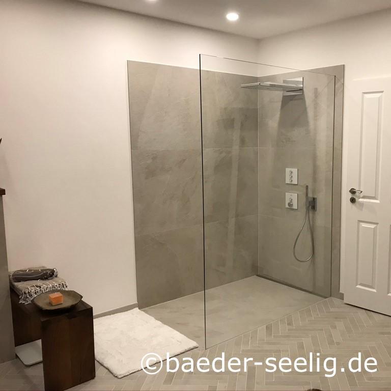 Abgebildet ist eine grosse begehbare duschkabine, die in einer wandecke eingebaut ist. Die beiden duschwaende sind ca. 2 m hoch mit xxl fliesen gefliest, der duschbereich ist mit derselben xxl fliese in betonoptik gefliest. Dadurch ist die dusche fast fugenfrei. Die freistehende ganzglas-duschabtrennung ist aus 10 mm sicherheitsglas, sie schliesst oben buendig mit der xxl wandfliese ab. Die unauffaellige v4a edelstahl-duschrinne pro ist an der schmalen duschwand wandbuendig passgenau zwischen wand und glasduschabtrennung eingebaut. Die dezente, schmale abdeckung aus gebuerstetem v4a edelstahl ist unauffällig. Die flachste duschablaufrinne nach mass sorgt mit ihrer konstant sehr hohen ablaufleistung von ca. 1 l/s fuer einen sehr schnellen ablauf des wasserschwalls aus der grossen regenbrause. Die begehbare duschkabine nach mass konnte durch die passgenaue sonderanfertigung der cm-geau angefertigten bodenablaufrinne hier im baubestand trotz der geringen moeglichen aufbauhoehe realisiert werden.