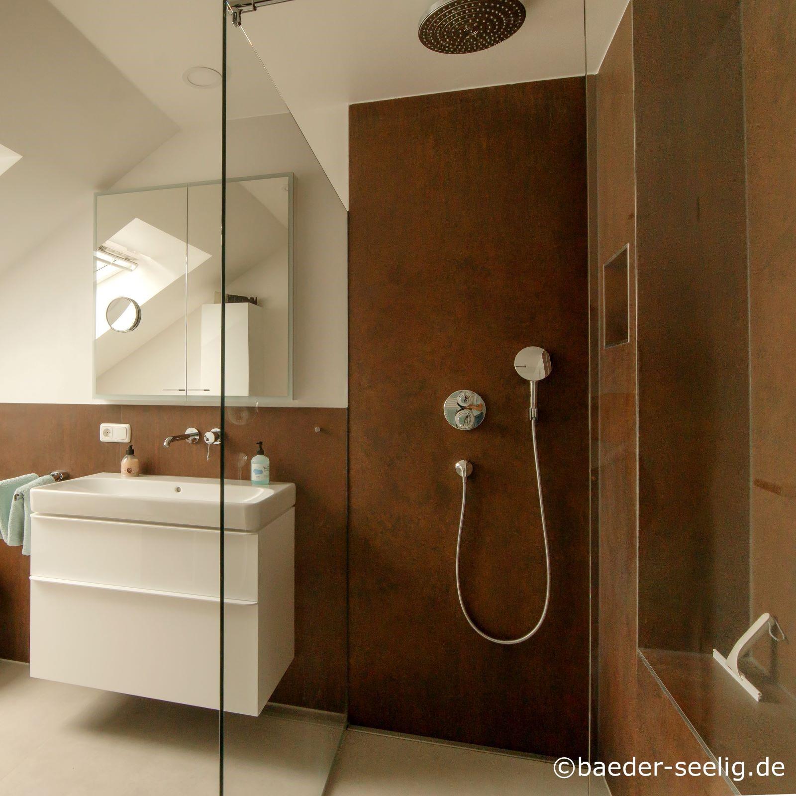 Abgebildet ist eine walk-in-dusche nach mass in einer wandecke rechts im bad. Links neben der ganzglas-duschabtrennung befindet sich ein weißer waschtisch. Das bad ist halbhoch, die dusche in voller hoehe mit braunen kerlite xxl fliesen von cotto d'este gefliest. Der grosse regenwasser duschkopf und die handbrause sind sichtbar. Die wandbuendig zwischen glasduschabtrennung und wand eingebaute duschablaufrinne faellt kaum auf. Die v4a edelstahl-duschrinne pro hat eine sehr hohe ablaufleistung von ca. 1 l/s und ist damit ideal fuer die grosse regenbrause geeignet. Das wasser laeuft so sehr schnell ab. Die bodenablaufrinne mit einer sehr niedrigen einbautiefe hat die verwirklichung der bodenebenen duschkabine hier im altbau mit einer sehr geringen aufbauhoehe und hindernissen im boden erst moeglich gemacht. Sie ist cm-genau in einer sonderanfertigung genau fuer diese duschplanung eingebaut worden.